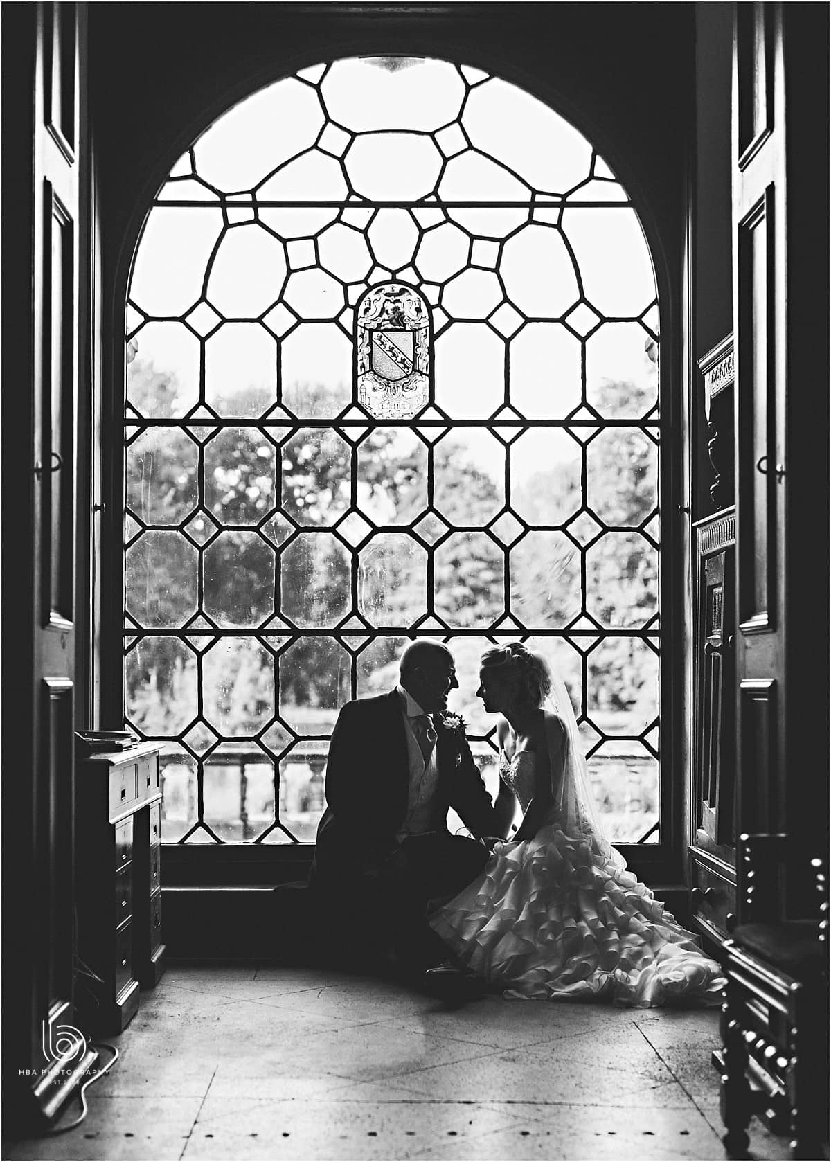 the birde and groom in the stunning leaded window at Thrumpton Hall