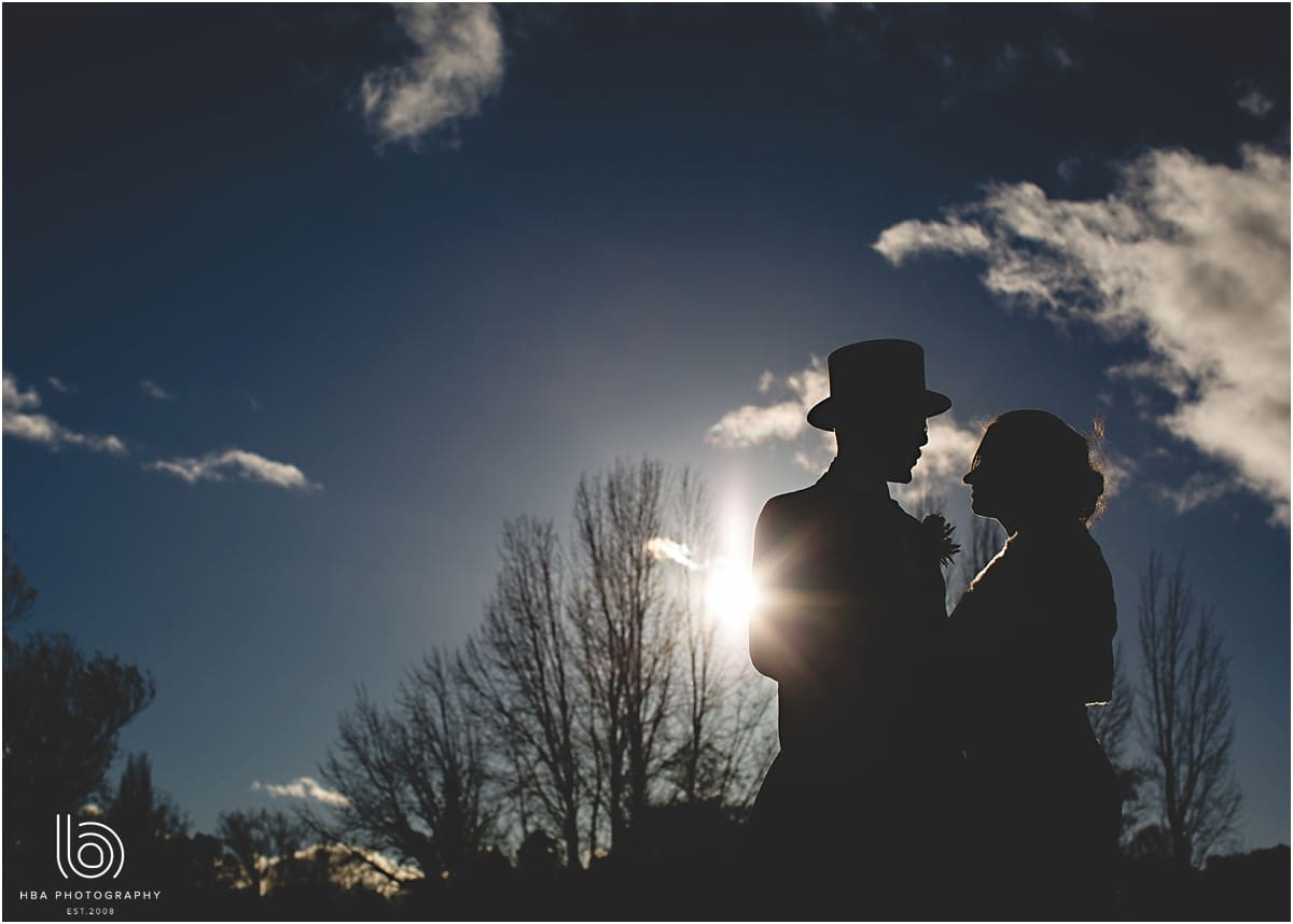 the bride and groom in silhouette by HBA Photography