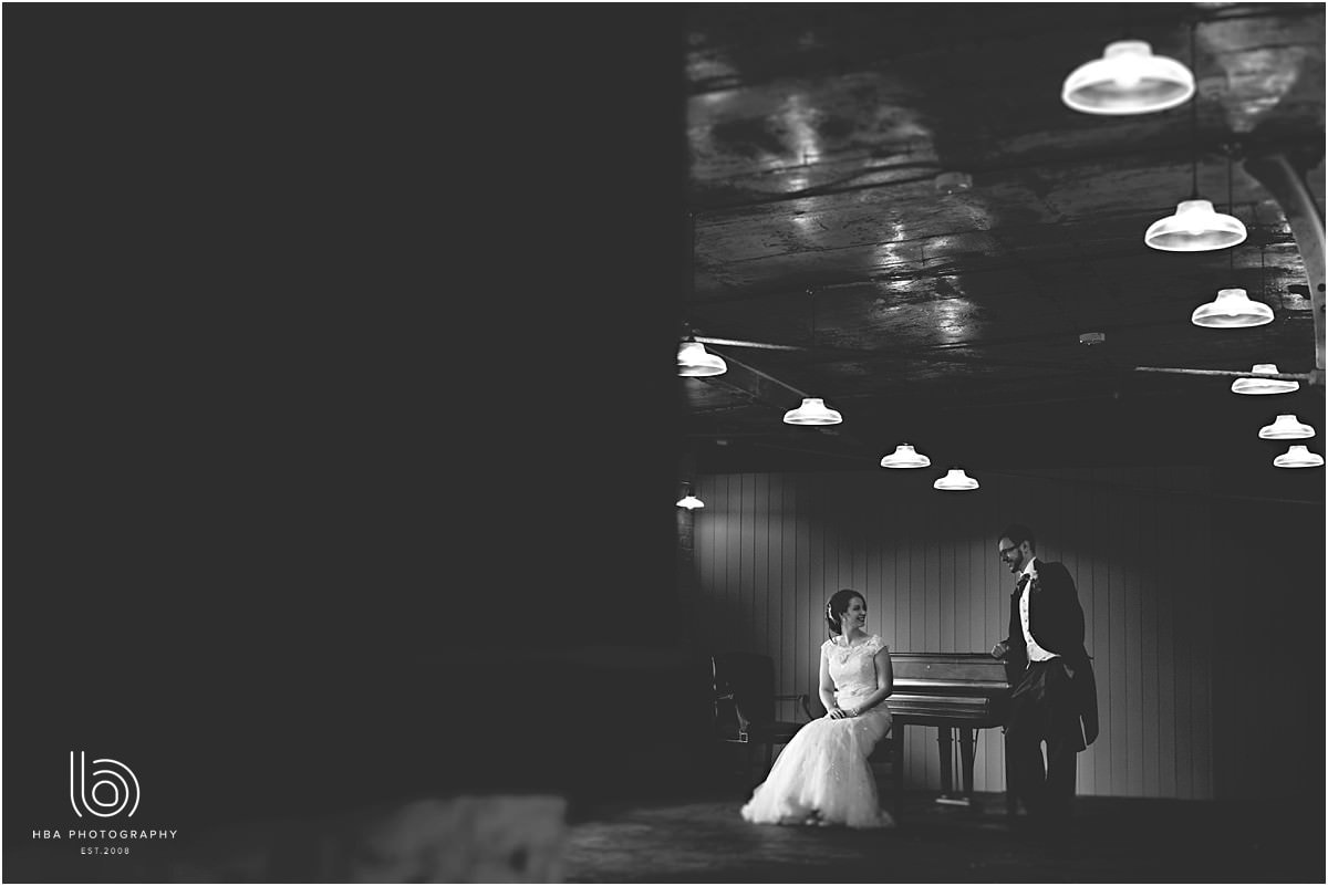 the bride and groom sitting by the piano in black & white