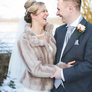 bride and groom in the snow laughing