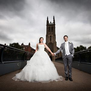 A bride and grom by a church with dark dramatic sky