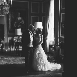 A black and white photo of a bride and groom stood by a large window