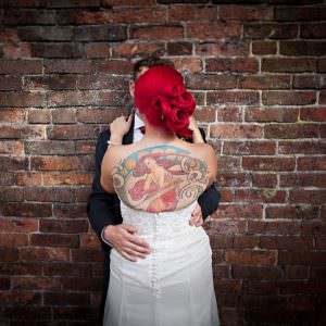 a tattoo'd bride hugging her husband