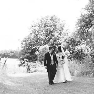 A black and white photo of a bride and groom walking from the church