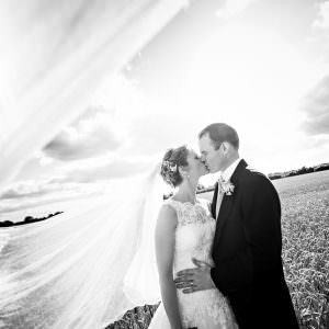 A bride and groom kissing in a field with her veil blowing in the wind