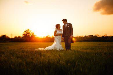 Bride and groom walking at sunset at Shustoke Farm barns