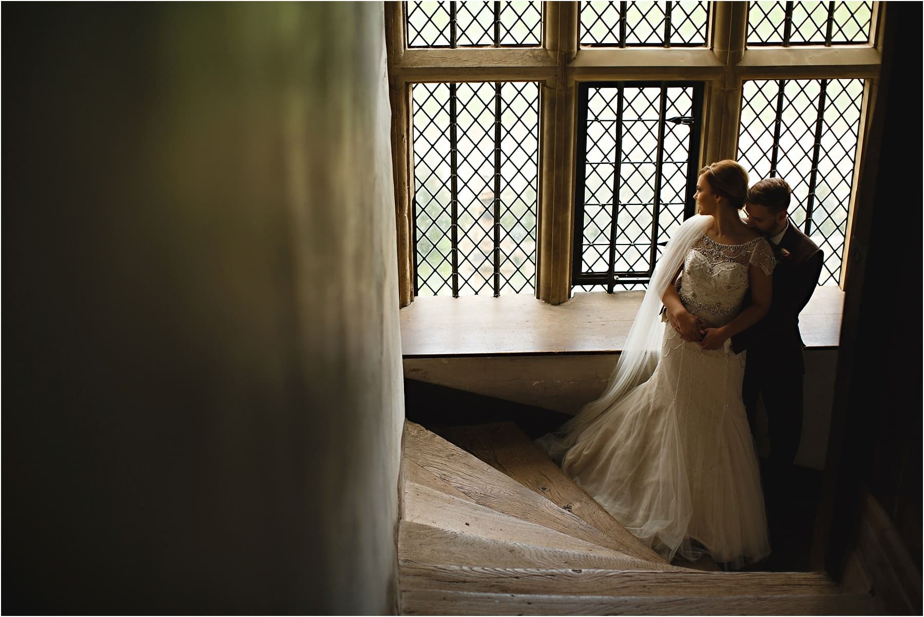 The bride and groom hugging in a stairwell at Hardwick Hall