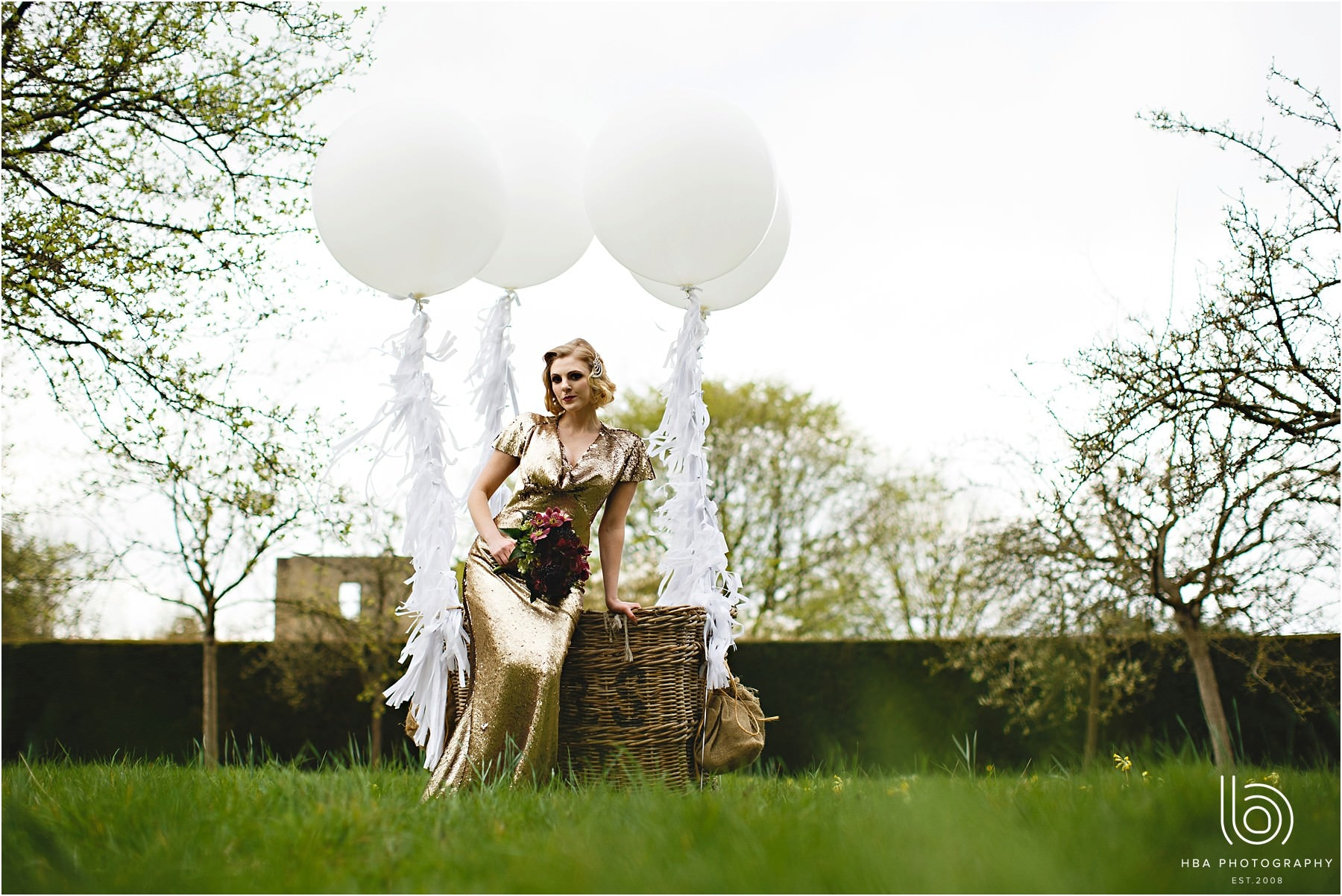 the bride in a balloon basket in the gardens on her wedding day at Hardwick Hall