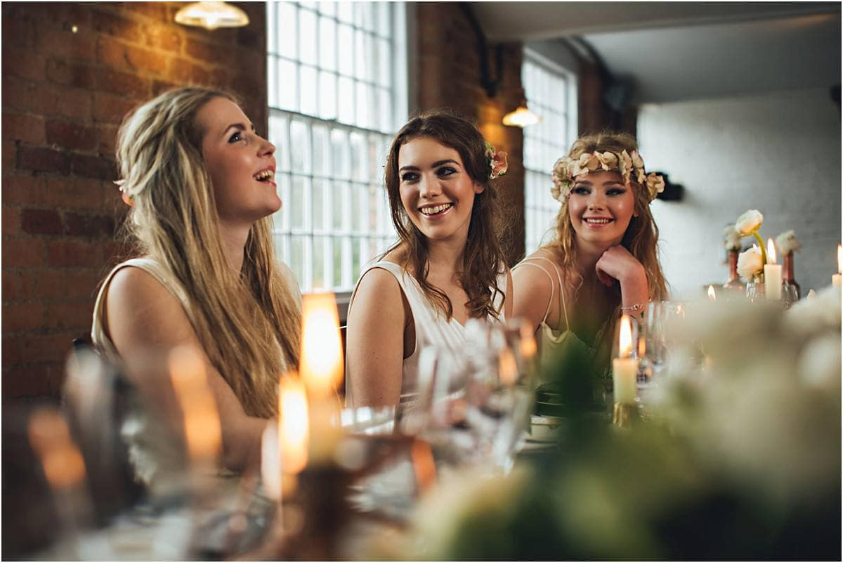 the bride and bridesmaids sat laughing at dinner time
