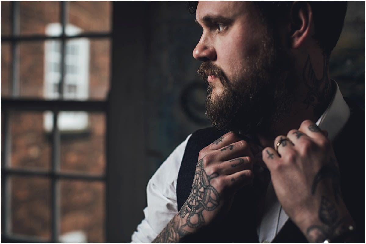 a groom with tattoos looking out of the window