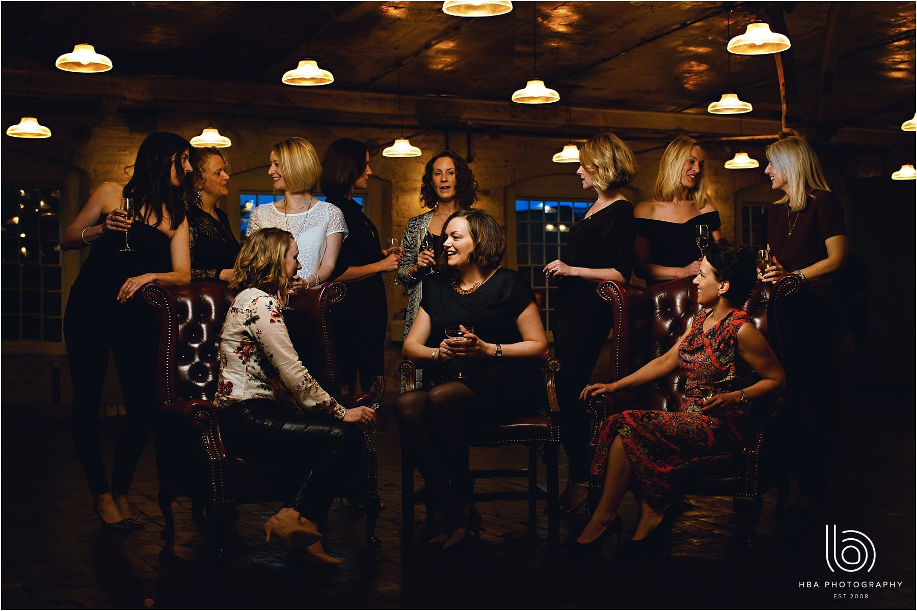 a group photo of all the girls in orange light sitting on chairs
