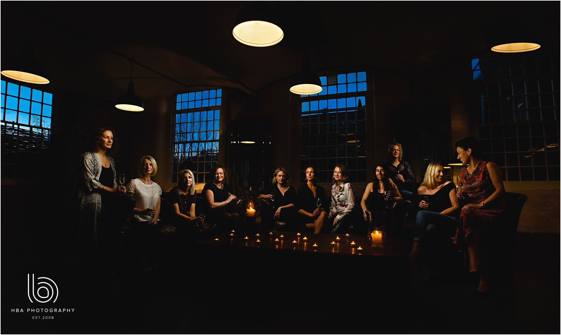 a cool blue group photo at The West Mill surrounded by candles