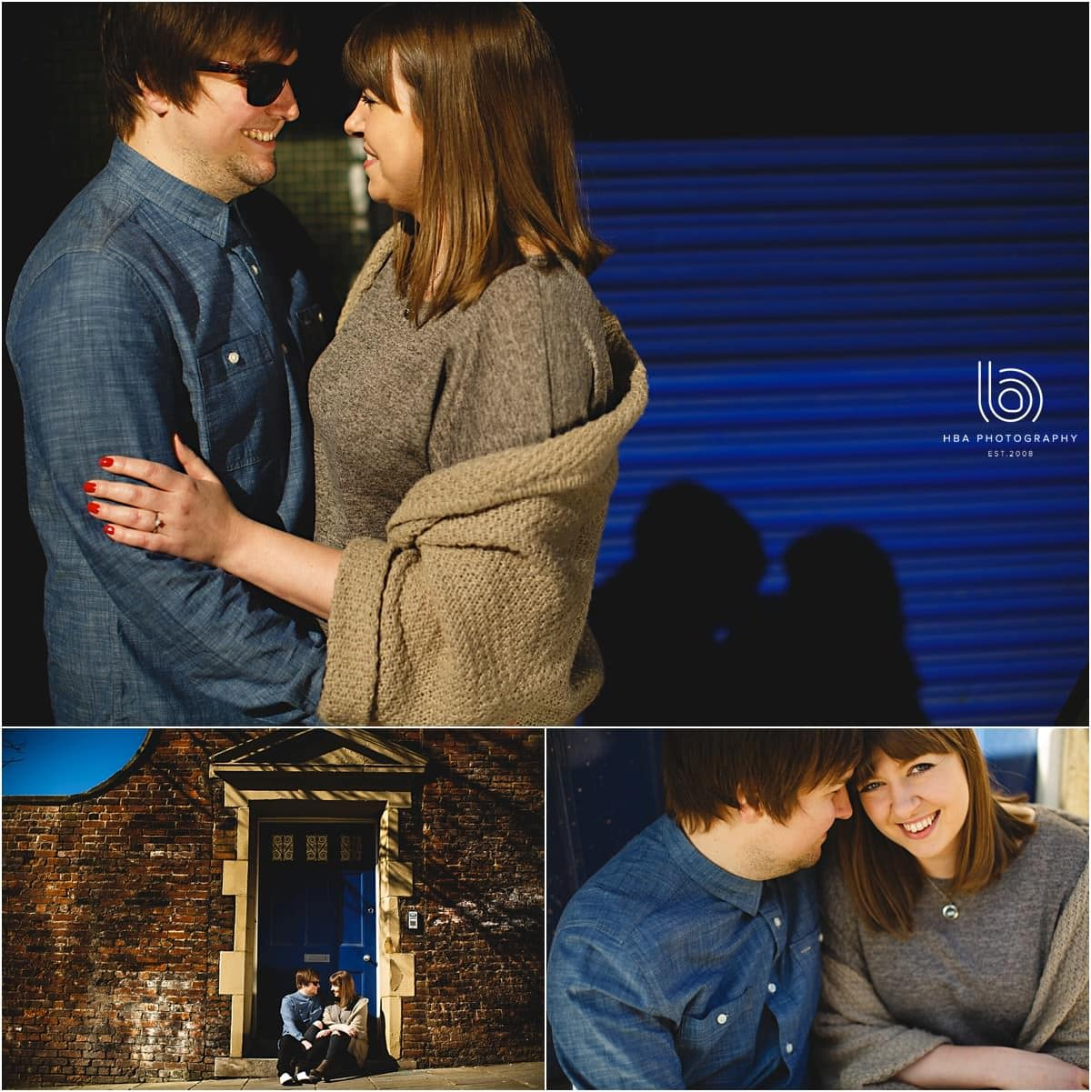 engaged couple looking at each other in front of a blue door