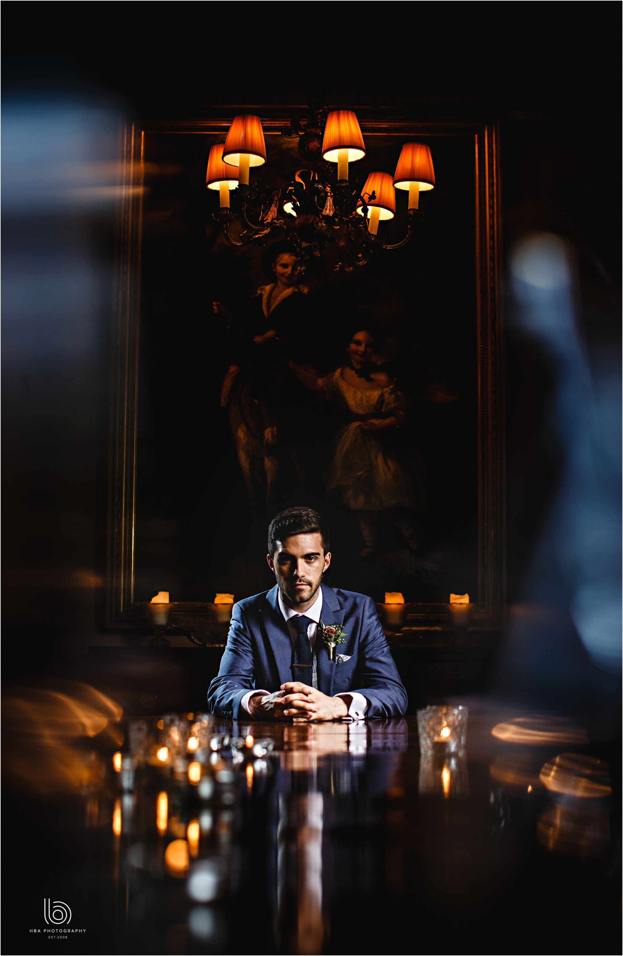 the groom sat at the wedding breakfast table surrounded in candles