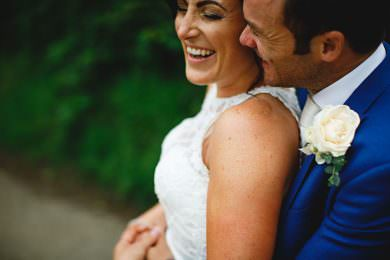 the bride and groom huggung dressed in white and a blue suit at Losehill House