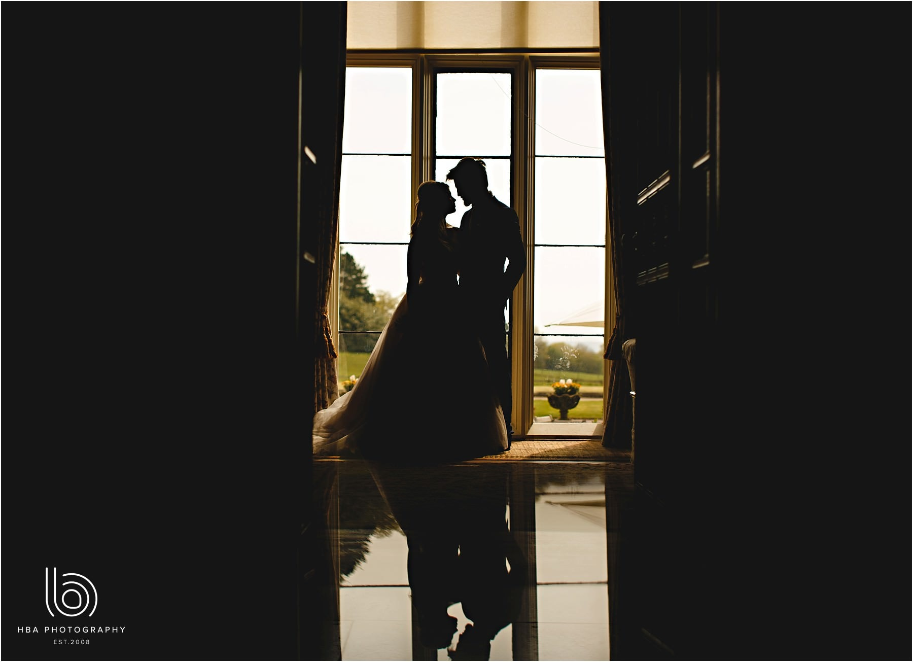 a reflection of the bride and groom in a window