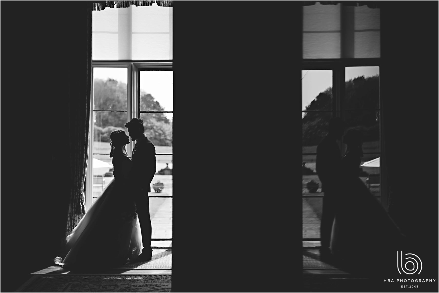black and white bride and groom stood in a window