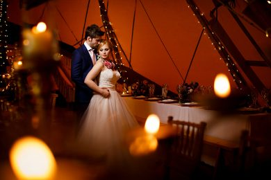 The bride and groom stood inside a tipi surrounded by orange candles