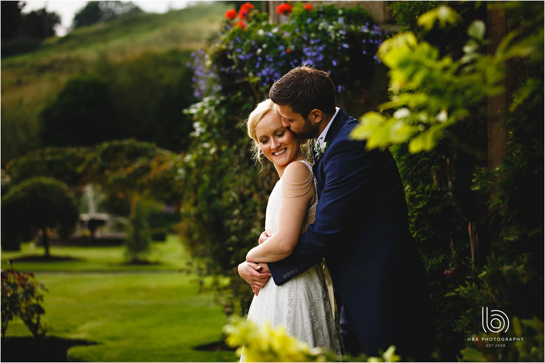the bride & groom in the gardens at cressbrook hall in derbyshire