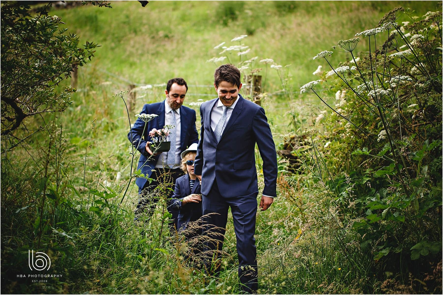 the groom & best mand coming down the hill to the venue