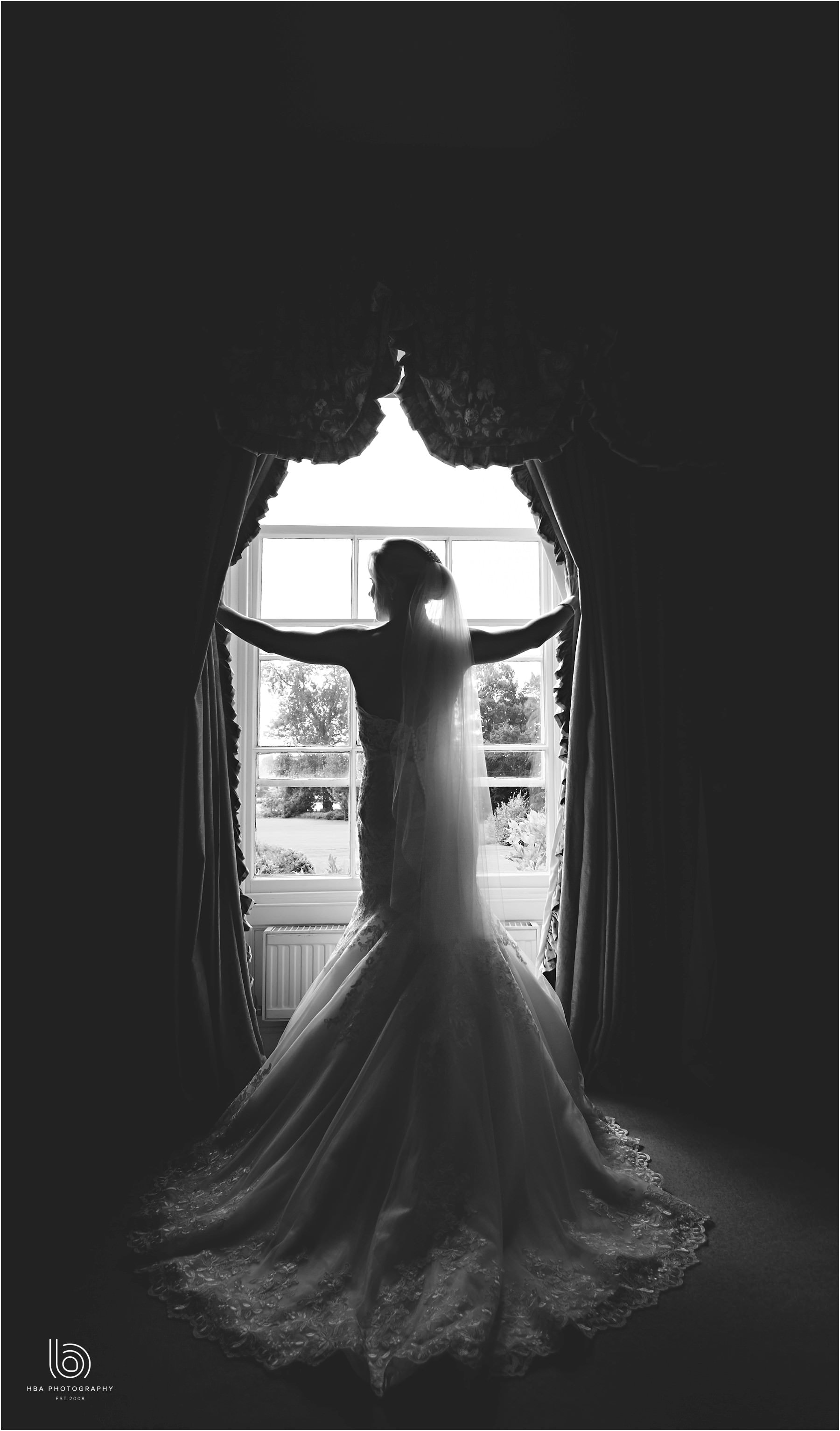 the bride holding back the curtains