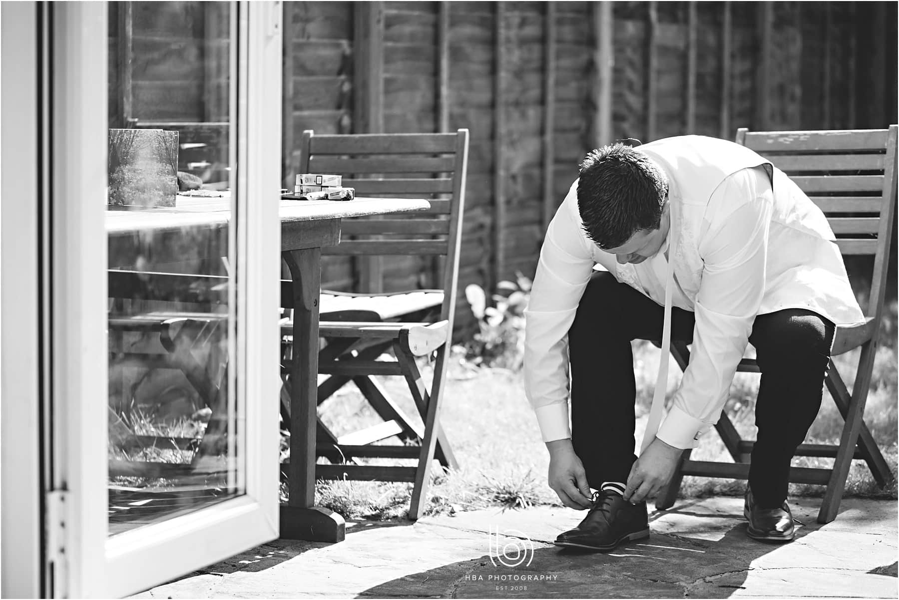 the groom putting his shoes on
