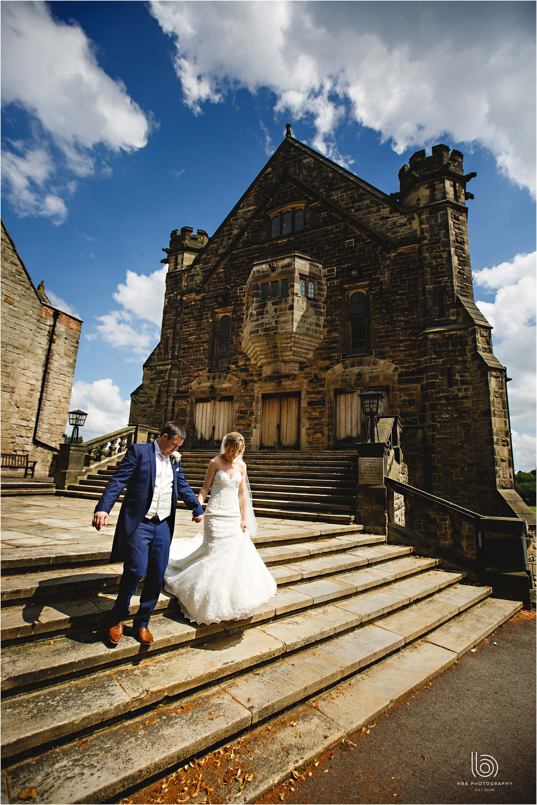 the bride & groom walking down the steps infront of Pears Hall at Repton School