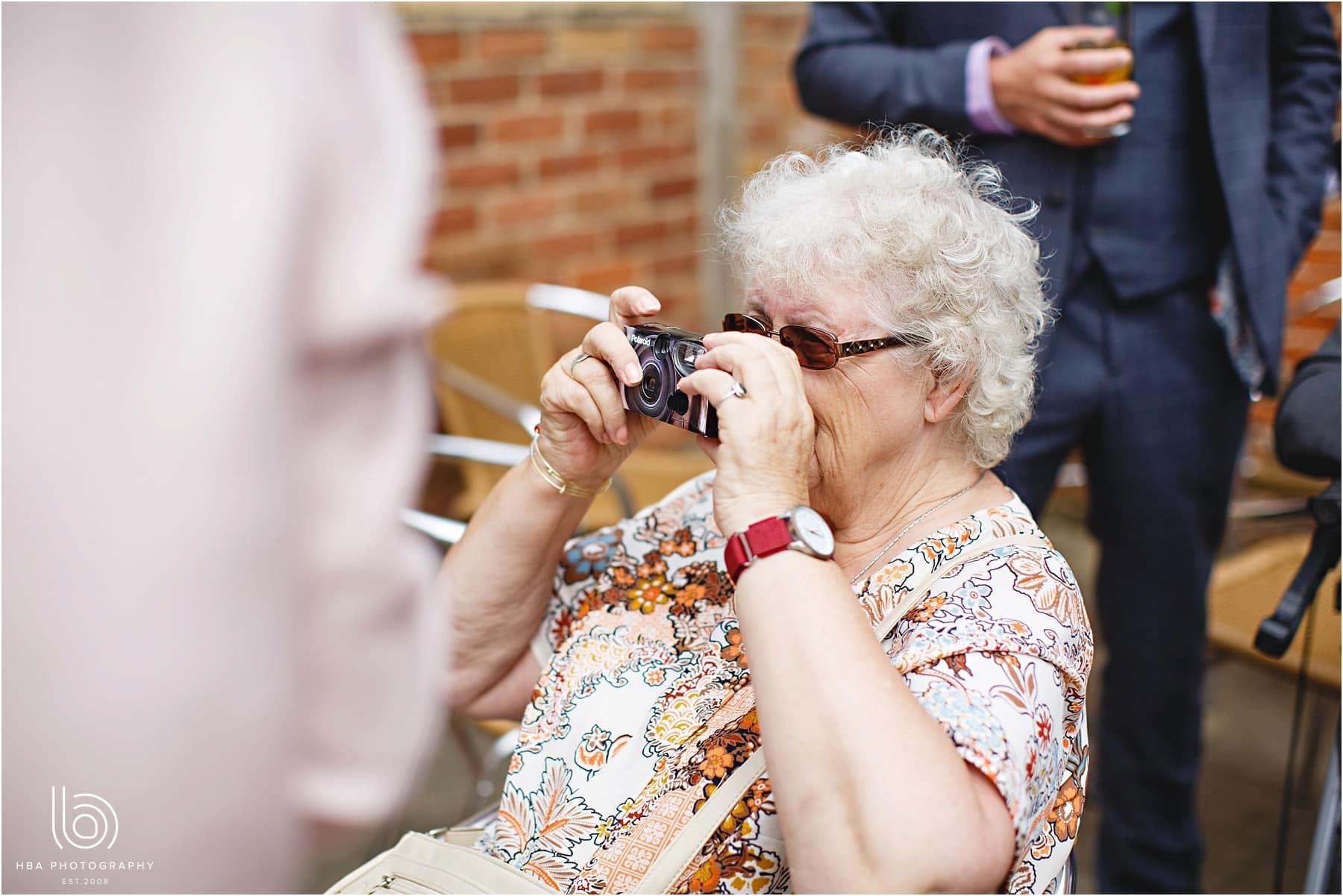 grandma taking a photo of the bride