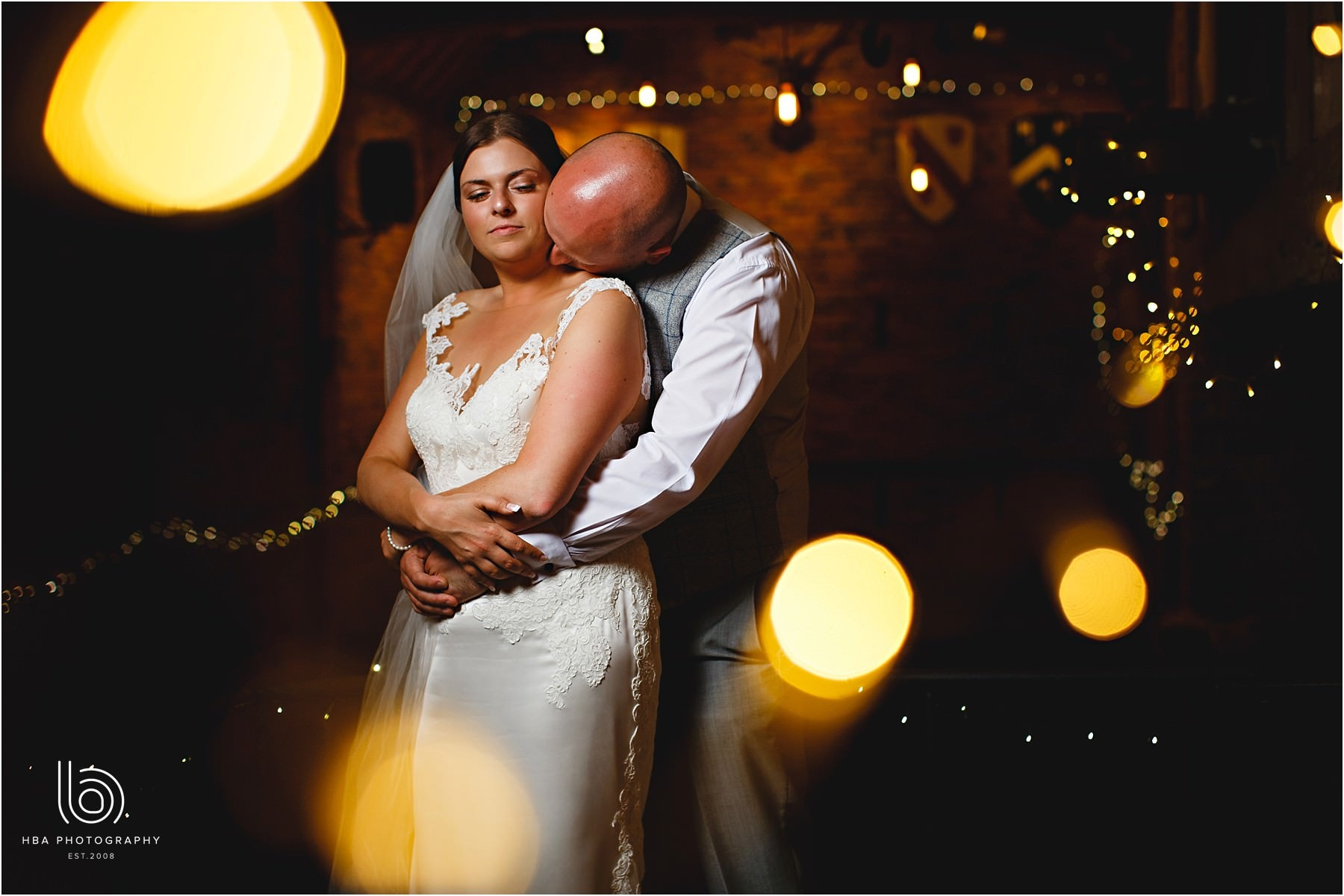 the bride & groom in twinkly lights in the Treshing barn