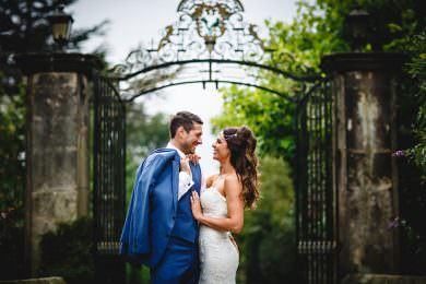 the bride and groom stood by the big gates at park hall farm