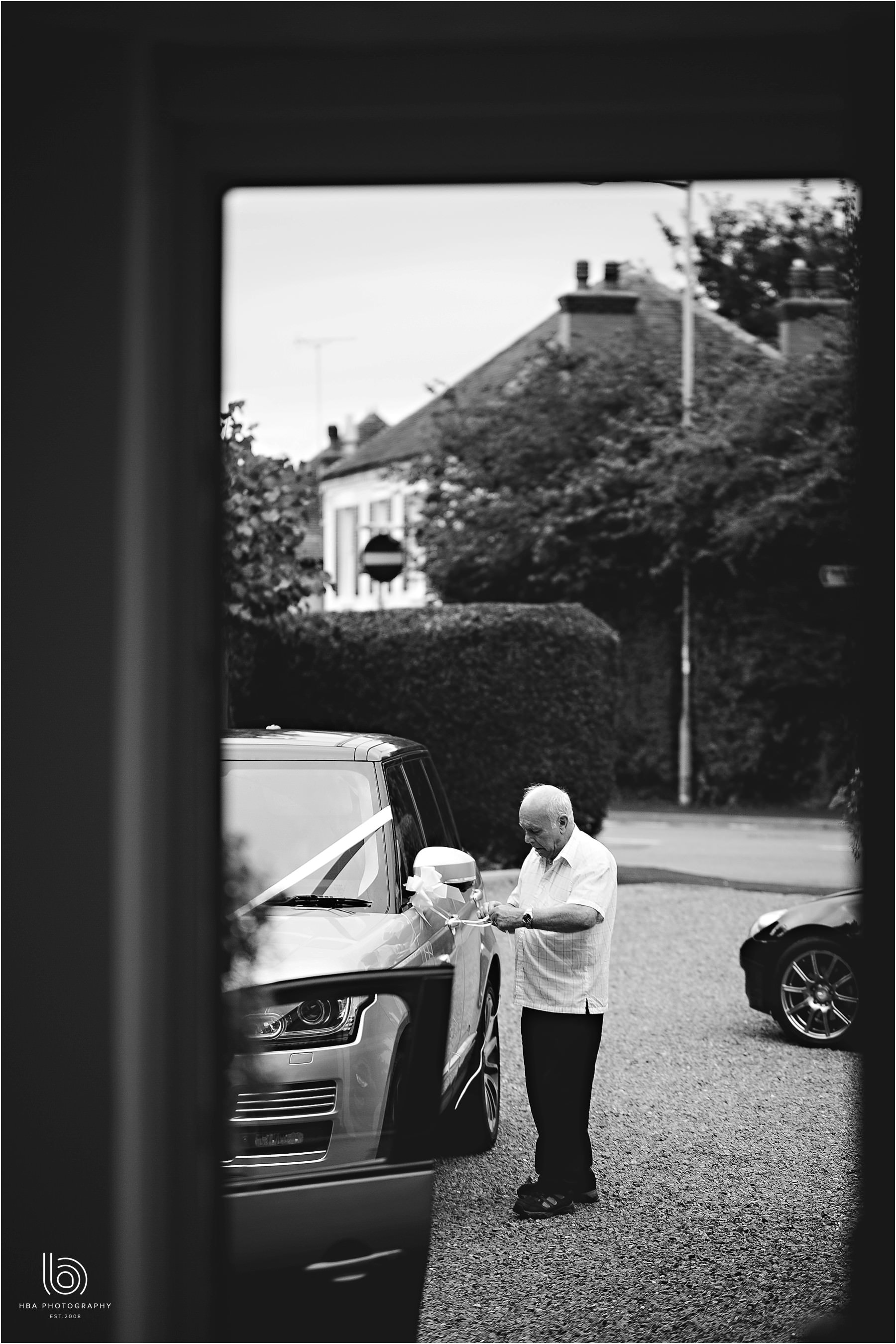 the father of the bride putting ribbons on the car