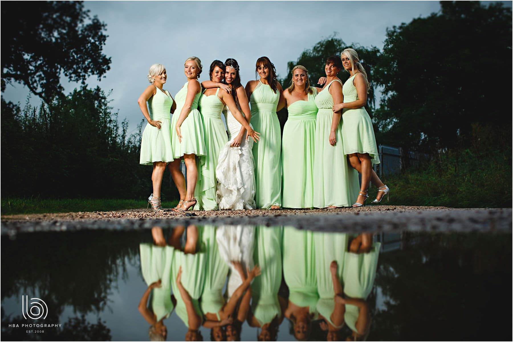 the bride & bridesmaids in a puddle