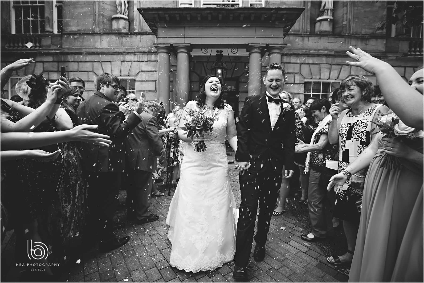a black and white photo with guests throwing confetti