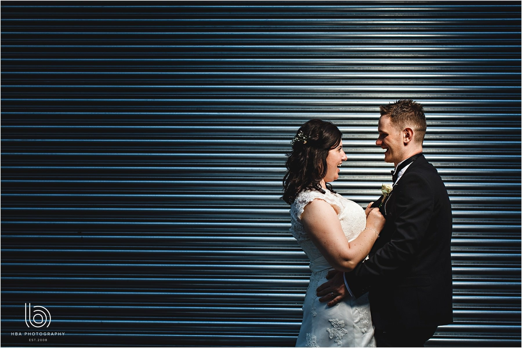 the bride and groom against blue shutter doors in the streets of Leicester City