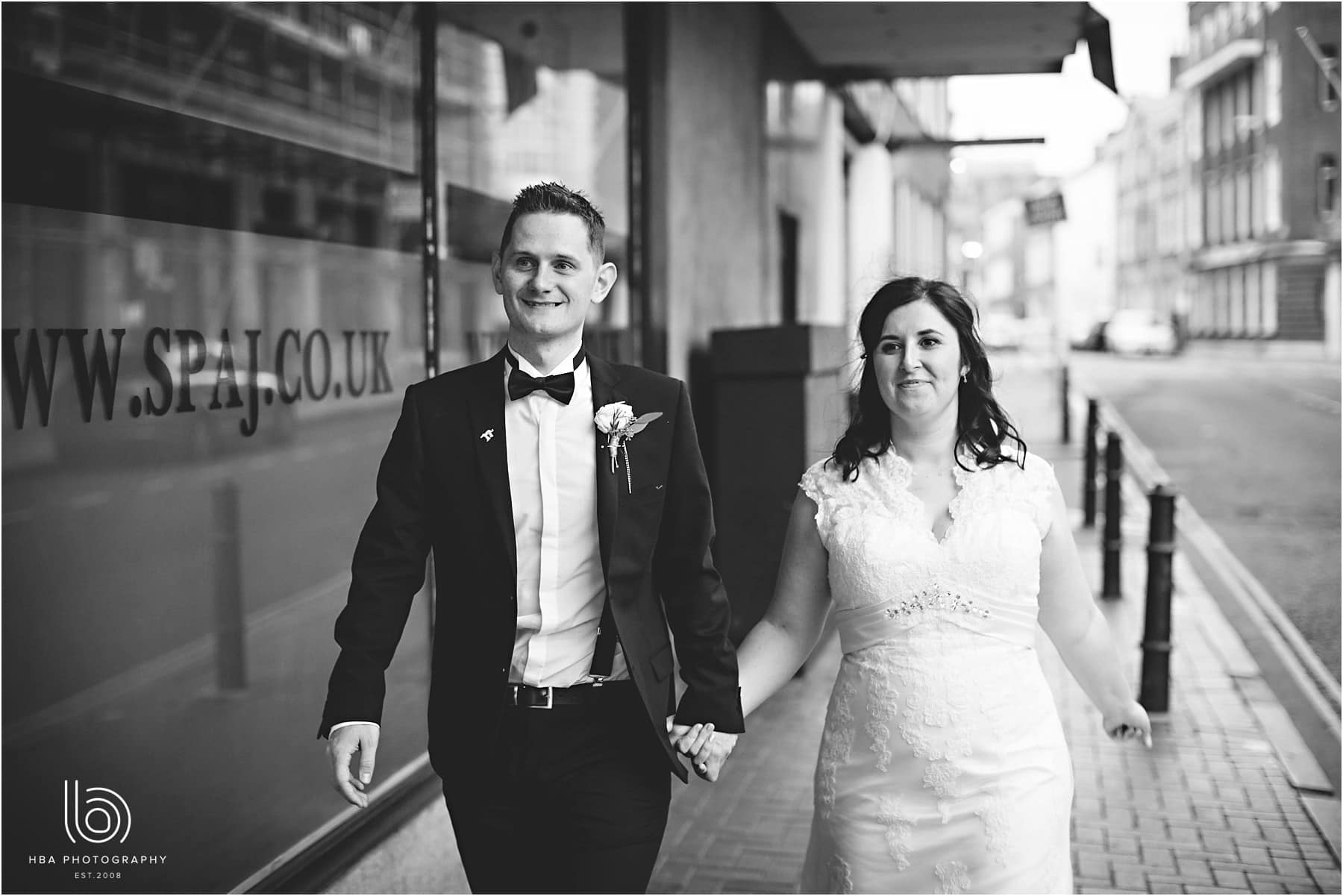 a black and white photo of the bride and groom going for a street walk on their wedding day