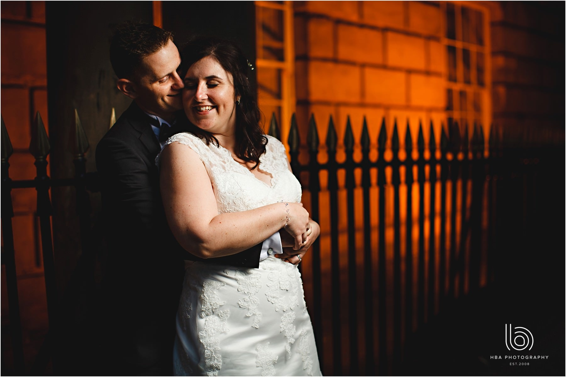 the bride and groom stood outside of the hotel in orange light