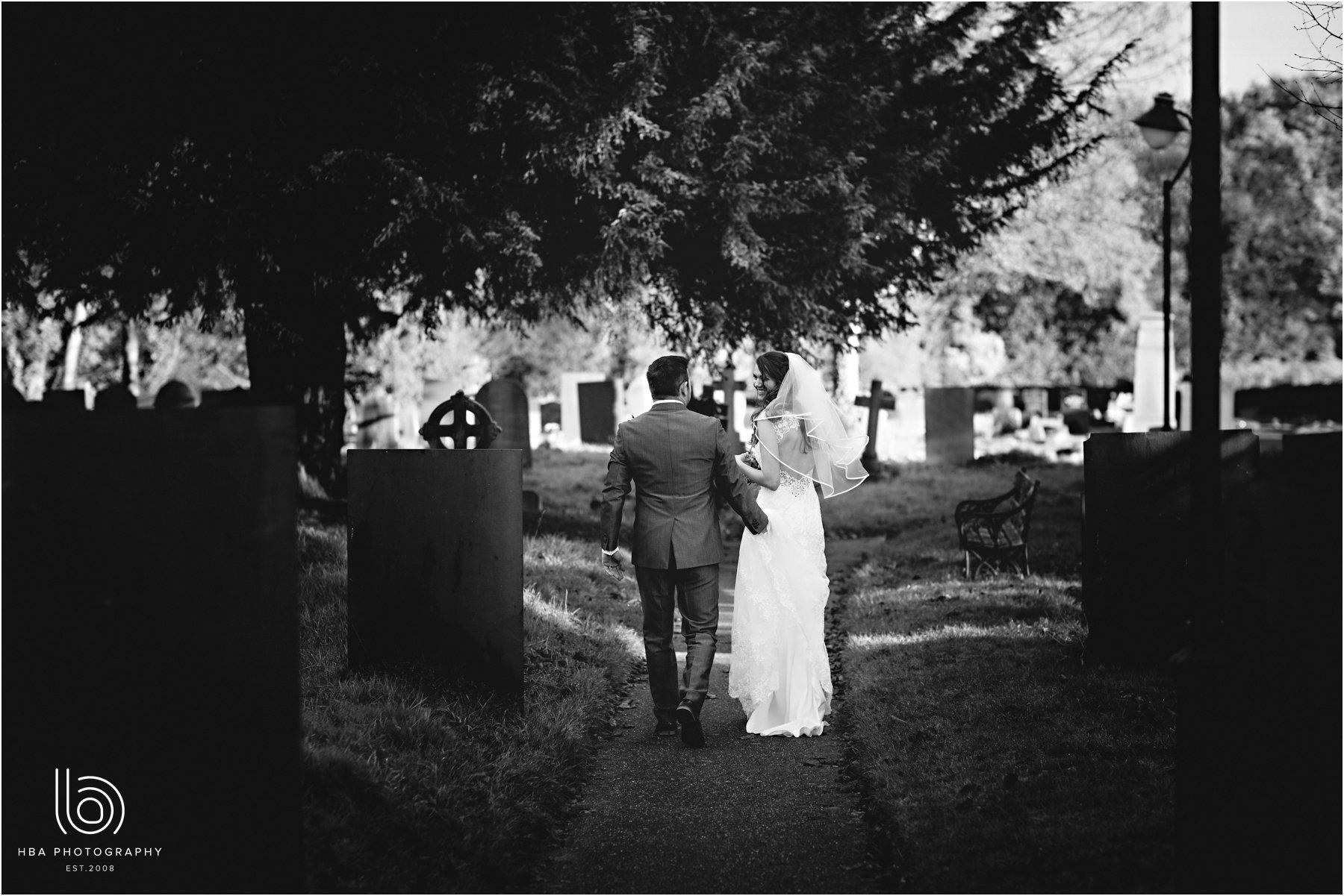 the bride & groom walking down the church path