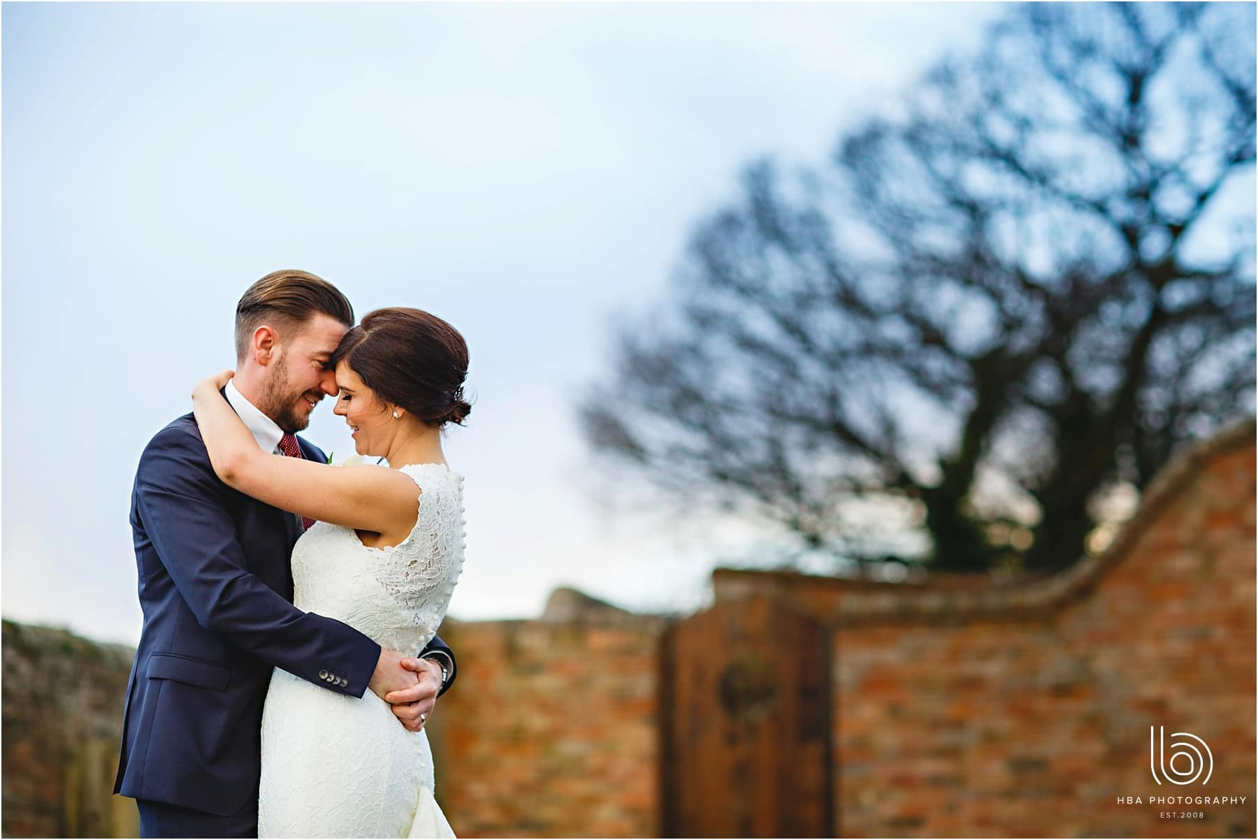 The bride and groom outside at Donnington Park farmhouse hugging together