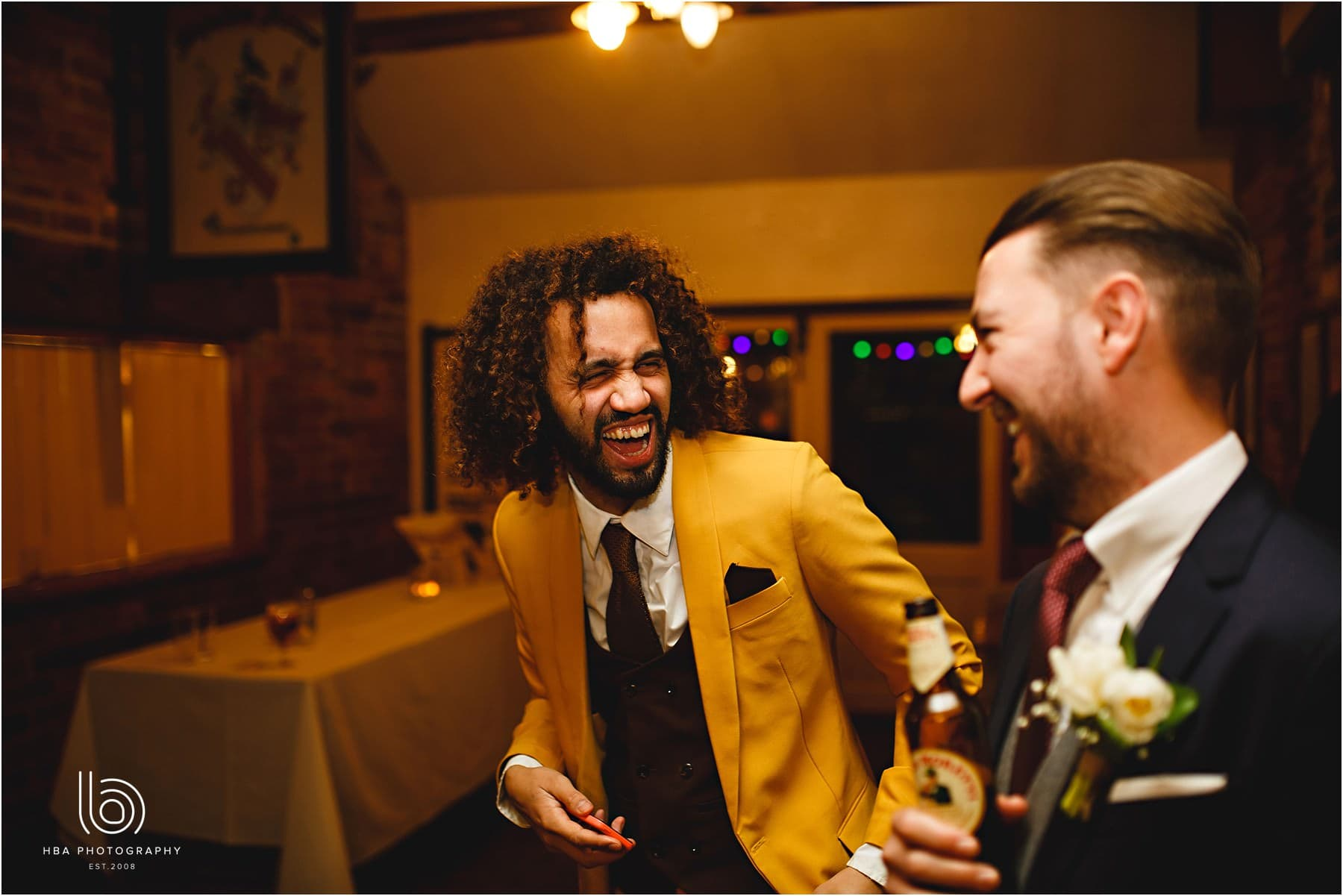 Wedding guest in a yellow suit having fun and laughing