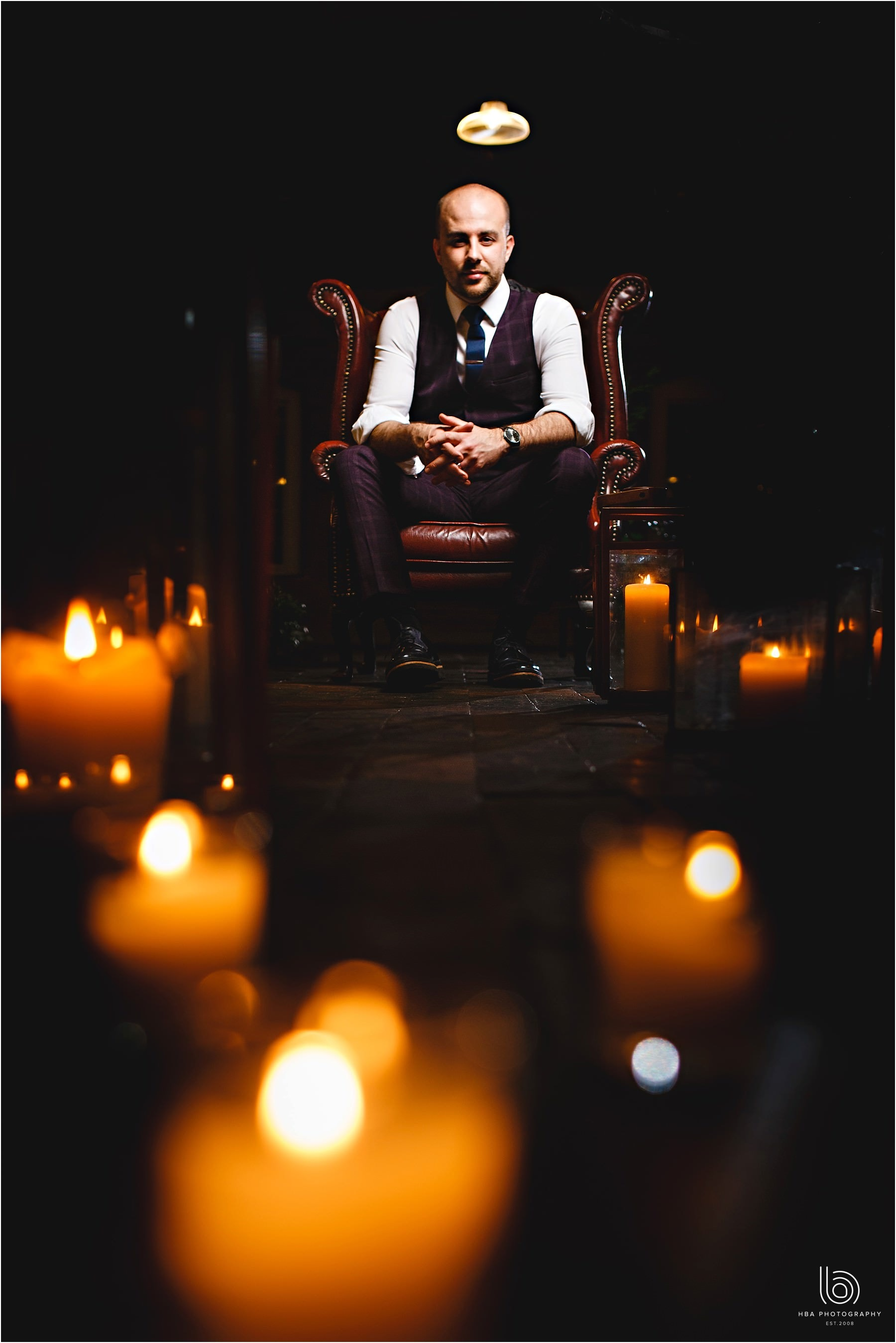 the groom surrounded by candles