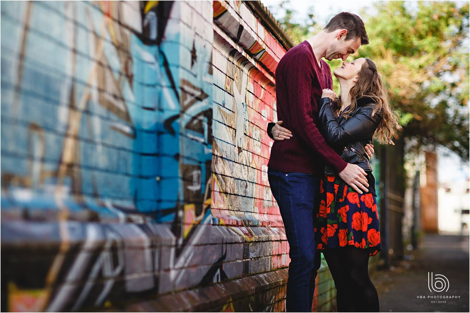 The bride and groom hugging each other by a graffiti wall