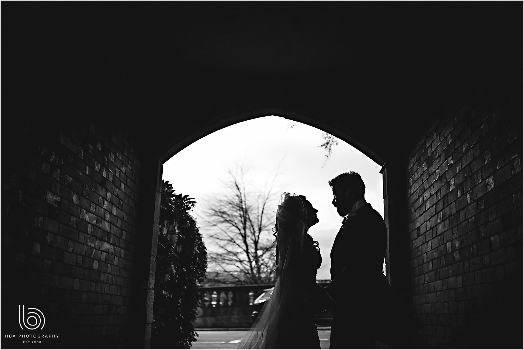 the bride and groom in silhouette at the church