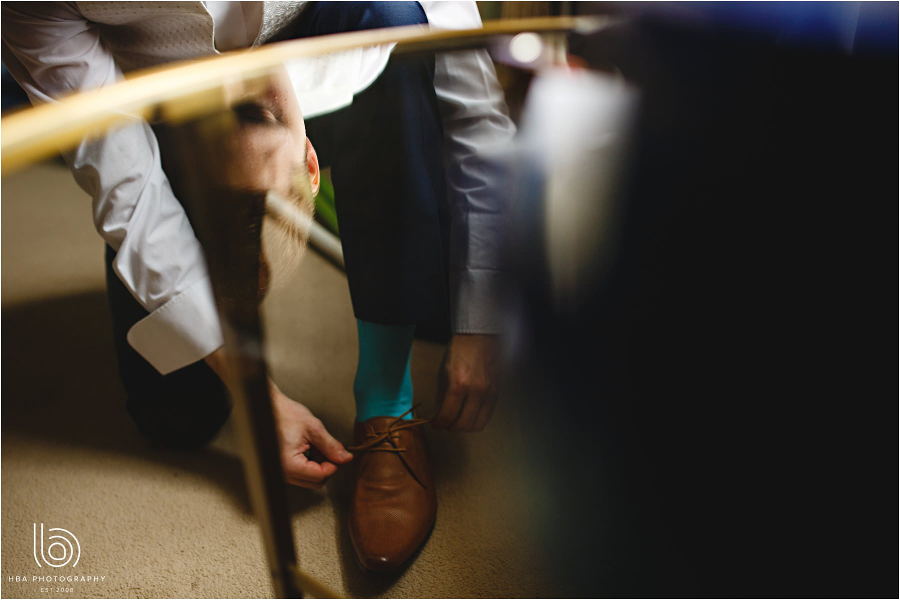 the groom doing up his shoes