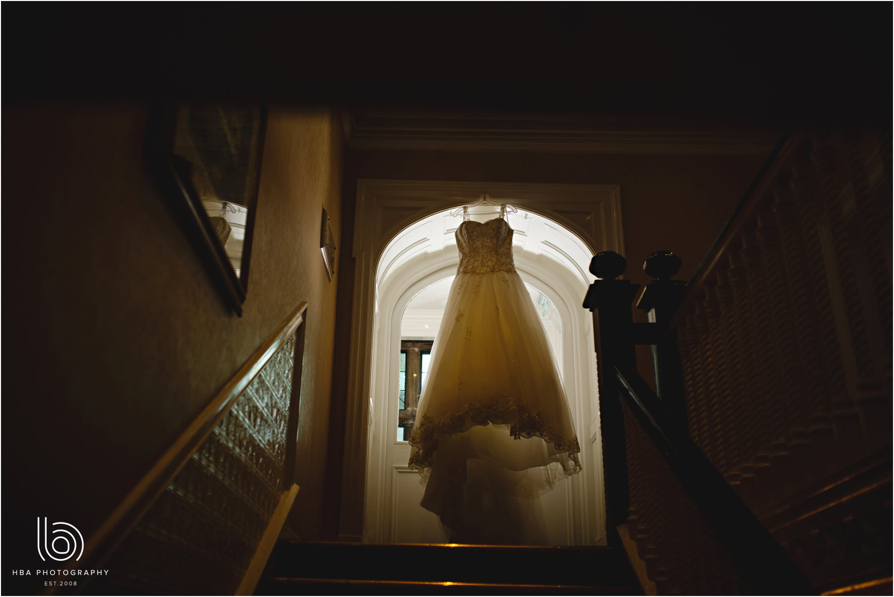 the bride's dress hanging on the landing
