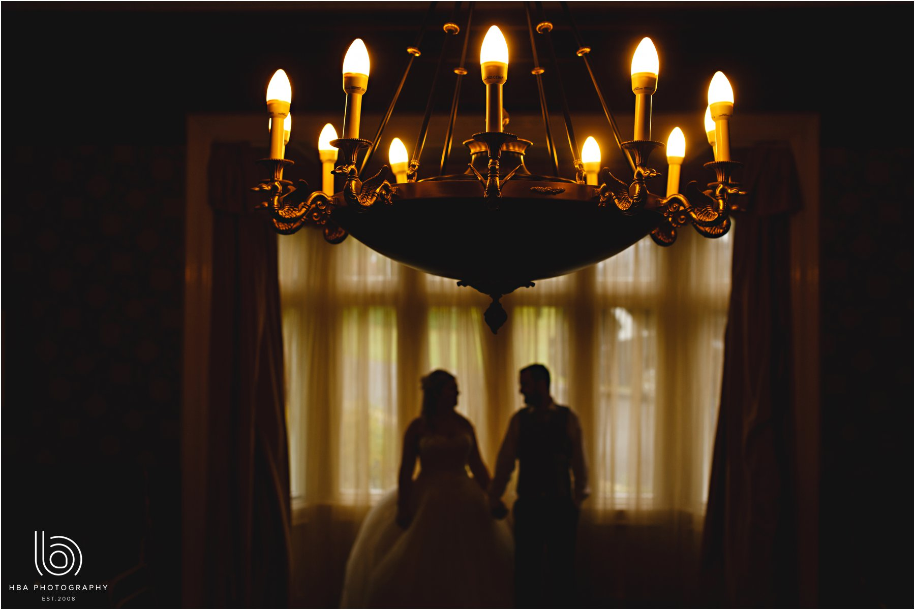 the bride and groom with the chandelier