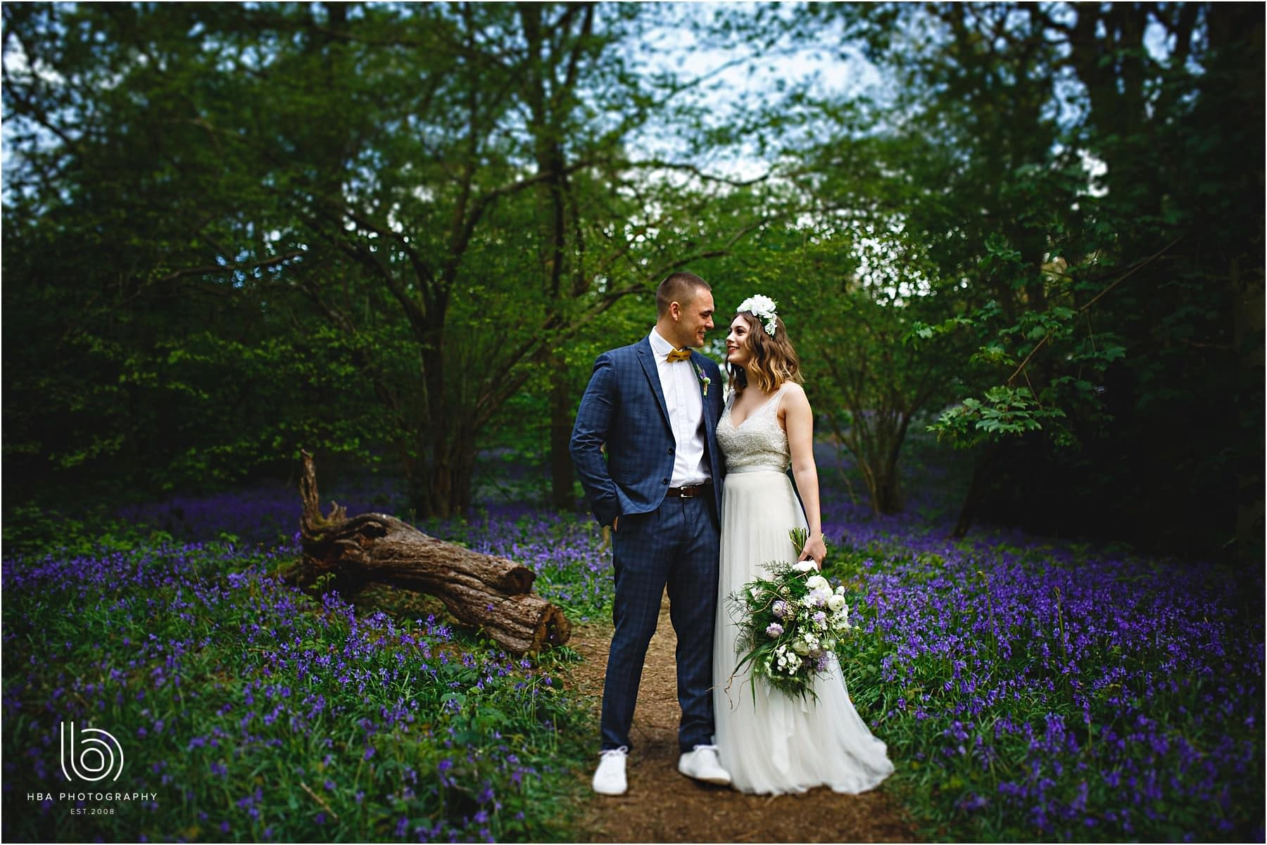 the bride and groom stood together in the bluebell woods woodland wedding