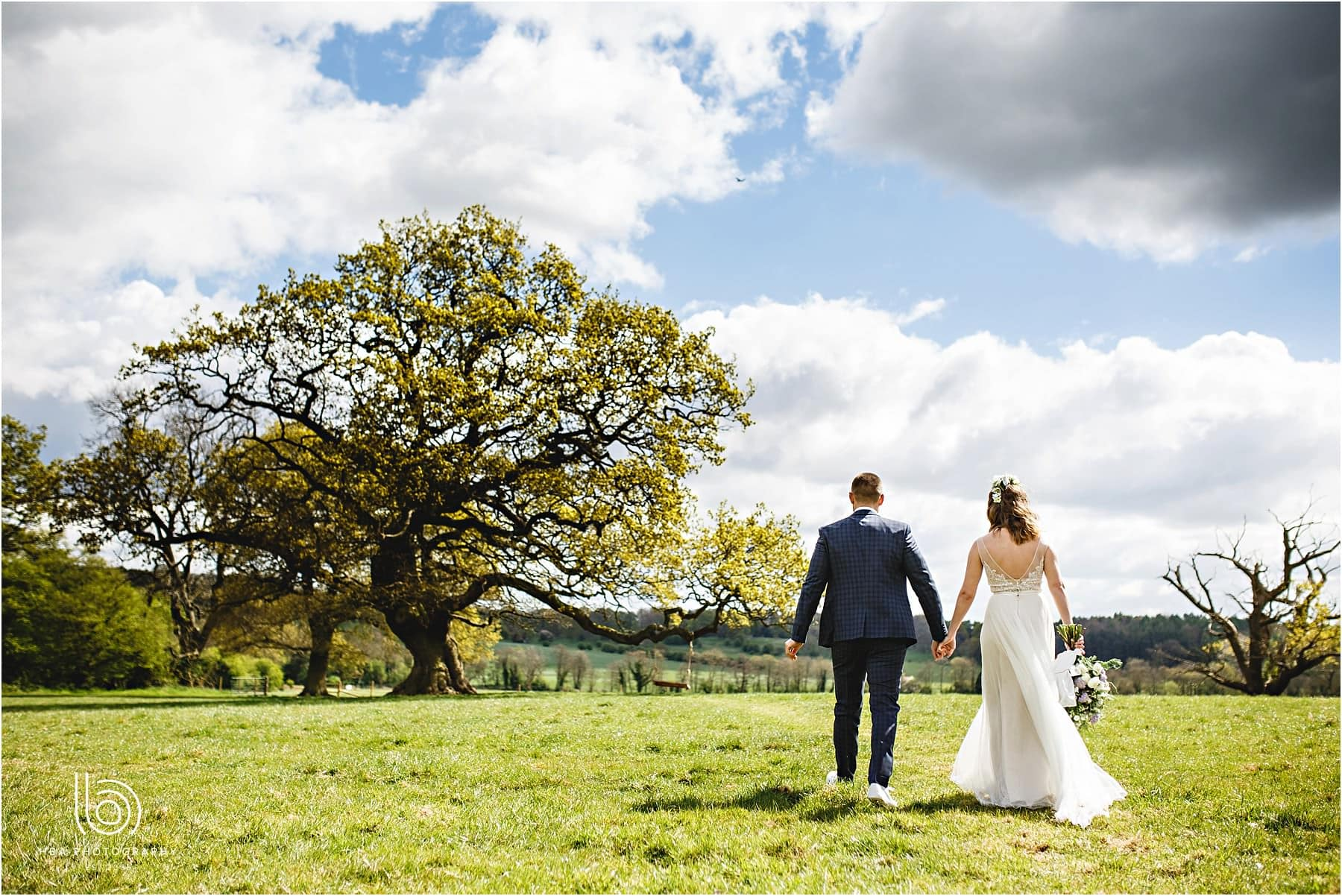the bride and groom walking accross the fields at the bluebell woods