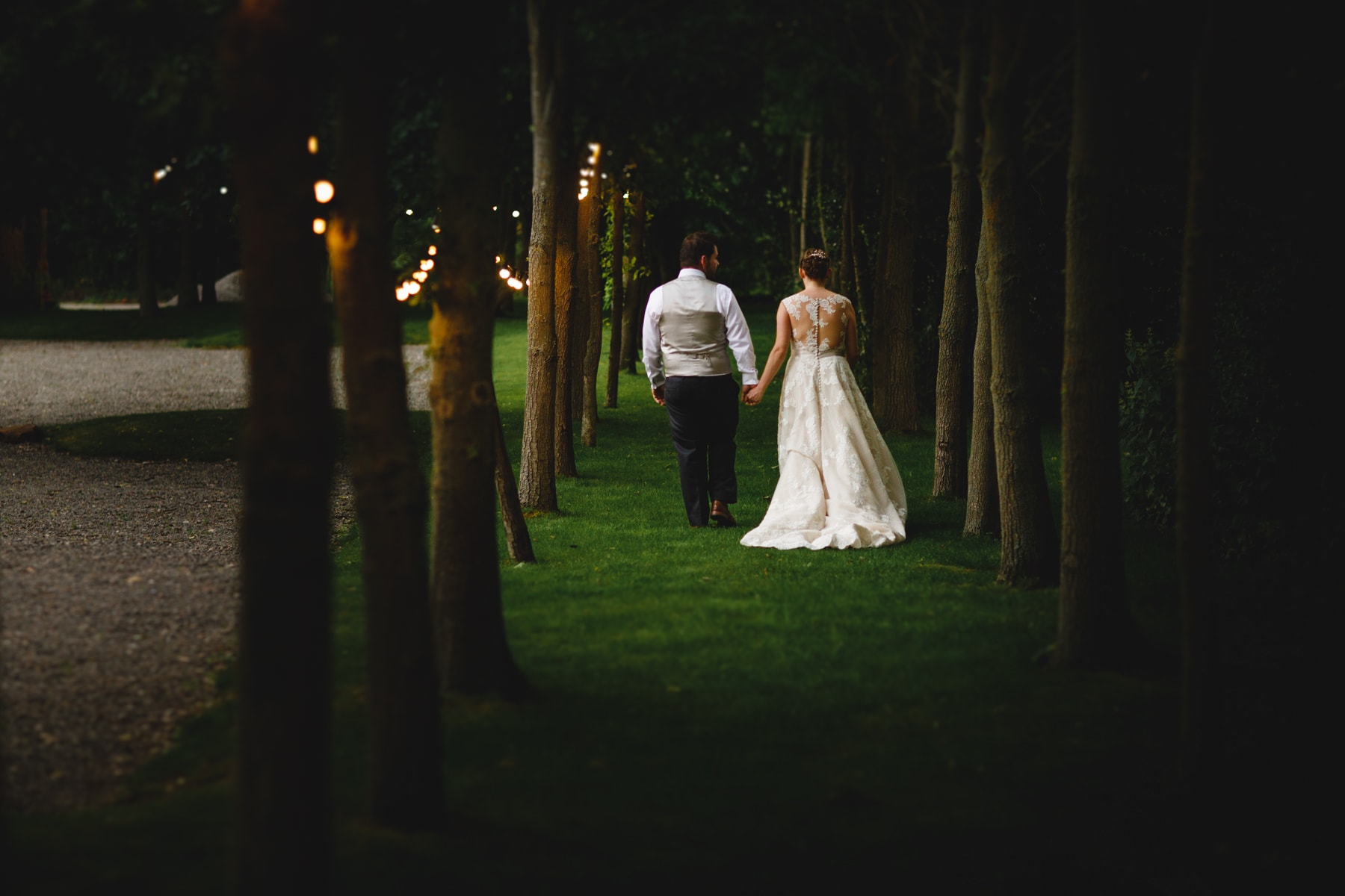 the bride and groom walking away in amongst orange fairly lights