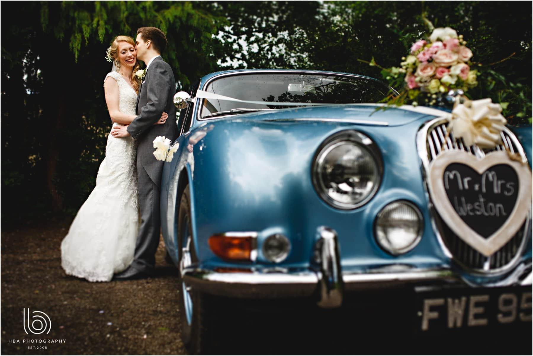 the bride & groom with their car