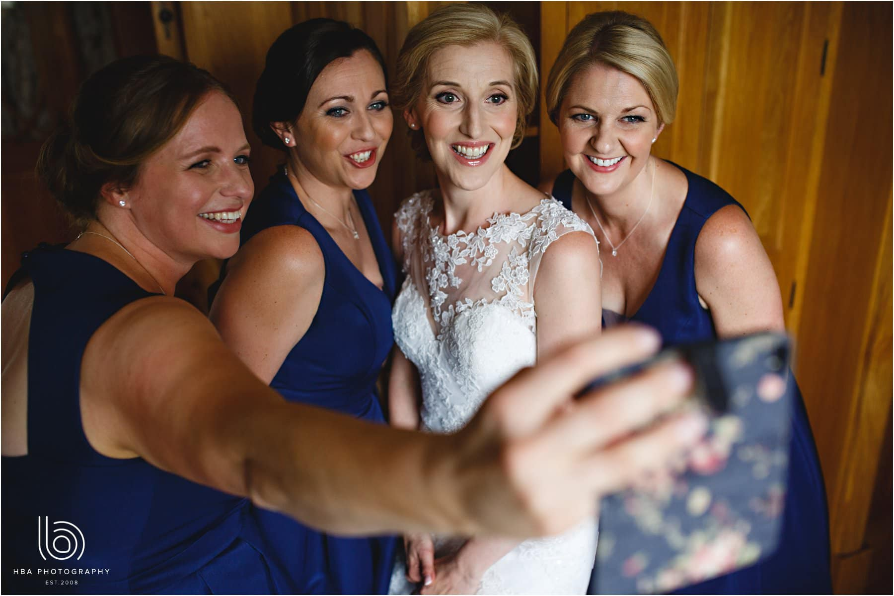 the bride and bridesmaids taking a selfie